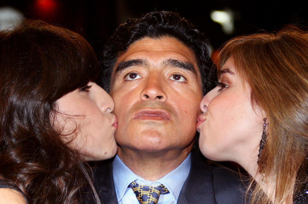 (FILES) In this file photo taken on May 20, 2008 former Argentinian football player Diego Maradona (C) is kissed bu his daughters Giannina (L) and Dalma as he arrives to attend the screening of Serbian director Emir Kusturica's documentary film 'Maradona by Kusturica' at the 61st Cannes International Film Festival in Cannes, southern France. - Argentinian football legend Diego Maradona passed away on November 25, 2020. (Photo by Valery HACHE / AFP)